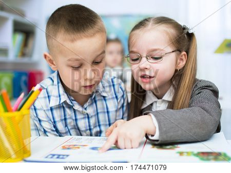 Little schoolchildren are reading book at school