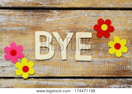 Word bye written with wooden letters on rustic surface and colorful flowers