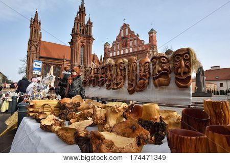 VILNIUS LITHUANIA - MARCH 4: Unidentified people trade traditional wooden masks in annual traditional crafts fair - Kaziuko fair on March 4 2017 in Vilnius Lithuania