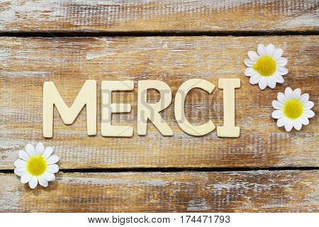 Merci (which means thank you in French) written with wooden letters on rustic surface and white daisy flowers