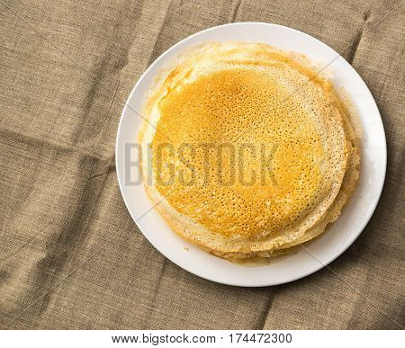 Stack Of Thin Pancakes On A White Plate Top View. Fresh Homemade Crepes Flat Lay