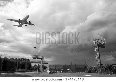 Airplane landing in Bologna Italy on a gloomy day full of clouds. In black and white