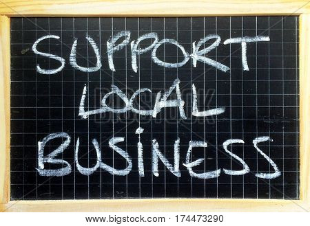 The words Support Local Business written by hand in white chalk on a blackboard as a reminder to buy goods and services in your community