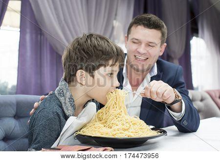 Dad feeding his son spaghetti in a restaurant