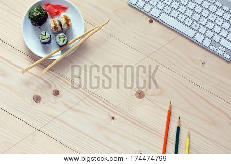 Natural handcrafted wooden Table in light brown color with Computer and color Pencils and Set of Sushi on Desk
