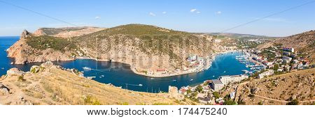Beautiful view of the Black Sea and the city Balaklava. Balaklava Bay. Genoese fortress in mountains. Clear summer day and a top view of the port
