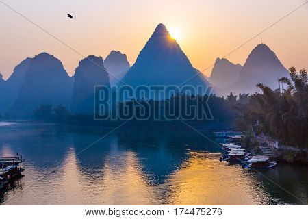 Traditional Chinese Sunrise Landscape with flow of River Water and Karst Mountains tropical Forest along the coast Boats bright Sunlight purple Morning Sky