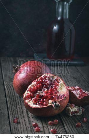 Broken pomegranats still-life with dark background. Toned