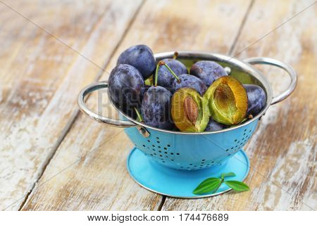 Juicy plums in blue colander on rustic wooden surface
