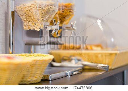 Cereal dispensers offering some kind of cereals on a self service breakfast in a hotel restaurant