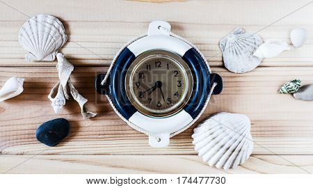 Decorative marine clock Lifebuoy on the background of wooden boards
