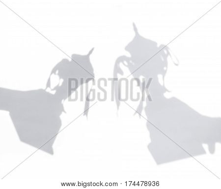 Shadow of hand holding trophy cup on white background.