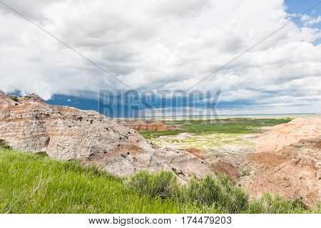 Dark blue storm cloud in Badlands National Park with prairie valley view
