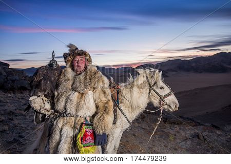Mongolian Eagle Hunter In Traditional Clothing, Holding A Golden Eagle On His Arm And Rider Horse On
