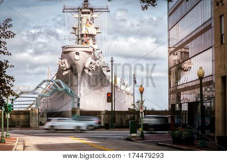 An east coast intersection with a World War Two era battleship as the backdrop.
