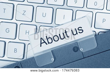 About us - folder with text on computer keyboard