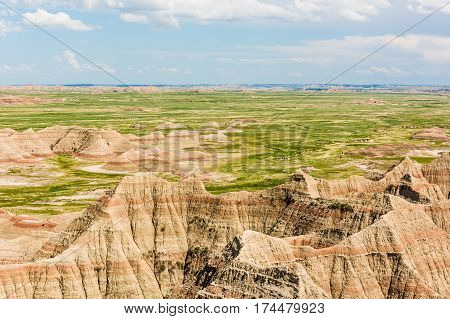 View of eroded Badlands canyons with green prairie valley