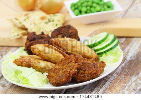 Selection of Indian snacks consisting of pakoras, onion bhaji and samosas
