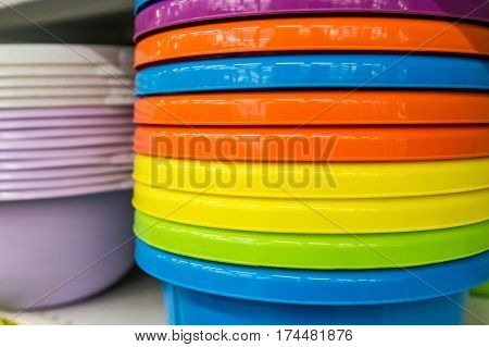 Many plastic washbowls of various colors in store