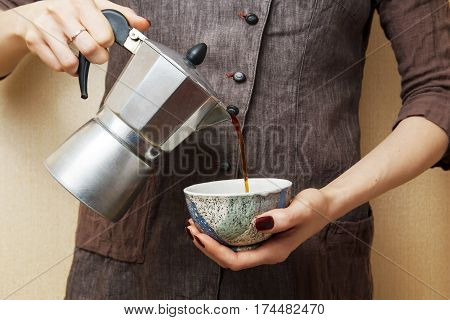 Preparing a cup of strong freshly brewed espresso coffee using a coffee geyser of the beverage pouring into a white cup on a dark shadowy background.