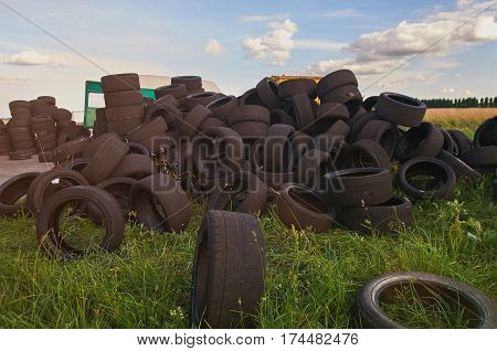 Stack of used tires lay on green grass background. Pile of used tires