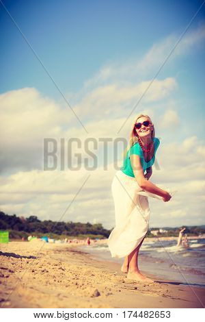 Woman On Beach Throwing Sun Hat