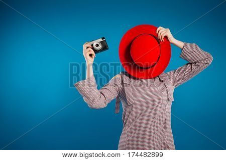 Stylish Girl Photographer With Camera, Red Hat And Clutch, Blue Background. The Concept Of Summer, P