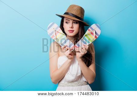 Beautiful Young Woman With Colorful Sandals Standing In Front Of Wonderful Blue Background