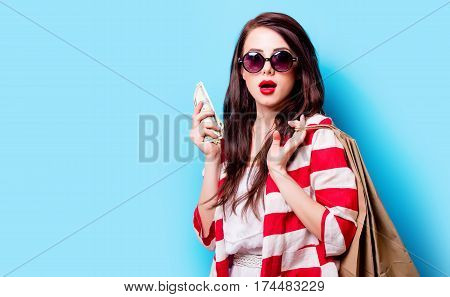 Beautiful Surprised Young Woman With Money And Shopping Bags Standing In Front Of Wonderful Blue Bac