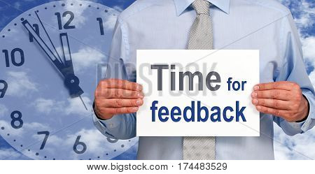 Time for feedback - Businessman with sign and clock in the background