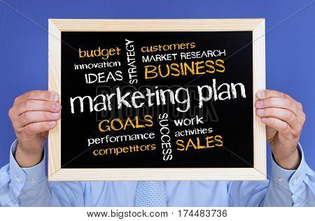 Marketing Plan - Businessman holding chalkboard with text