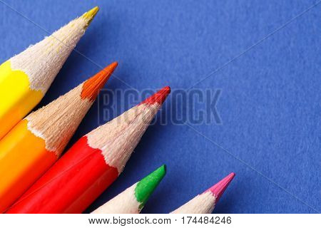 Colored pencils angle. Many different colored pencils on blue background. Macro. Close-up view. Art and design. Drawing and painting. Artist.