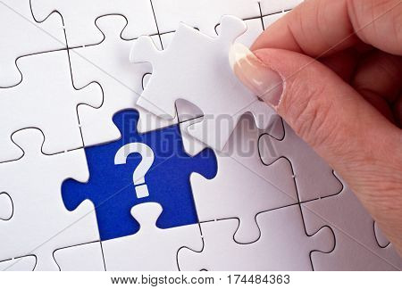 Question - female hand with puzzle and question mark