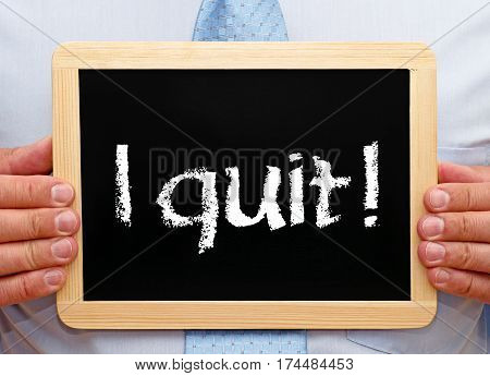 I quit - Businessman holding chalkboard with text