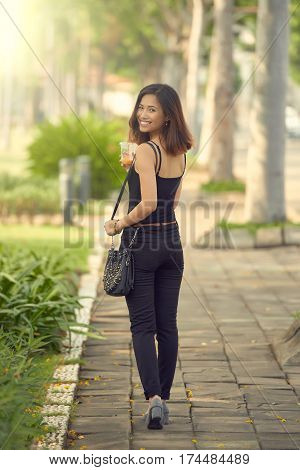Pretty young woman turning back and smiling at camera