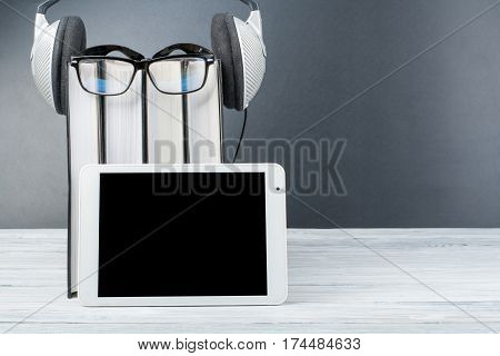 Audiobook on back background. Headphones put over stack of books empty cover copy space for ad text. Distance education e-learning concept. Tablet PC