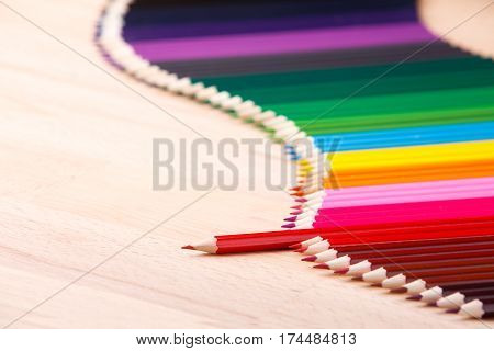 Multicolored pencils on beige wooden table. Waveform border from colour pencils. Copy space. Place for text. One red pencil stand out from other pencils.