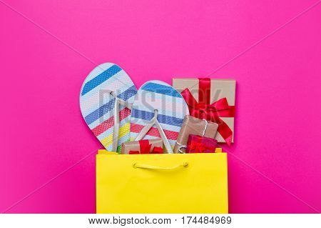 Cute Gifts And Cool Sandals In Shopping Bag And Cool Laptop On Wonderful Pink Background