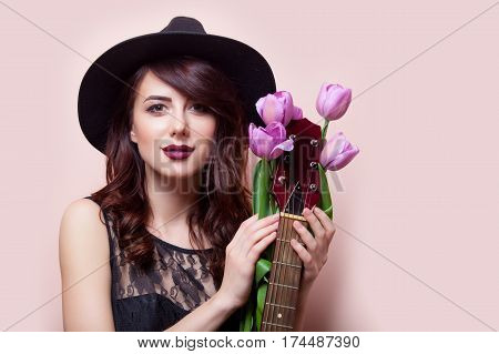 Beautiful Young Woman With Bunch Of Tulips And Guitar On The Wonderful Pink Background