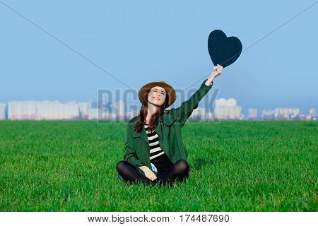 Beautiful Young Woman Sitting On The Grass With Heart Shaped Toy On The Wonderful Green Field
