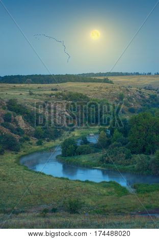 Beautiful full moon rising above the river valley with a a flock of birds