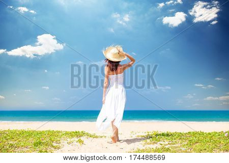 Beautiful Young Woman Standing On The Sand Beach And Looking At The Sea