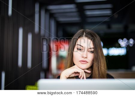 Entrepreneur woman working with a laptop in a coffee shop or home terrace