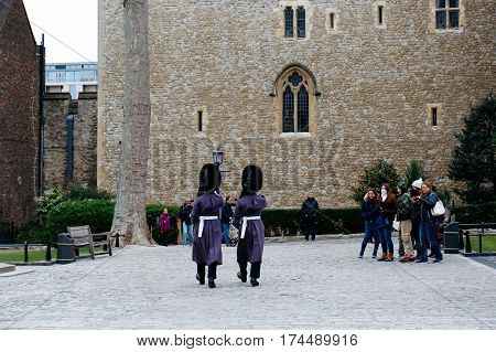 LONDON, UK - MARCH 30, 2016: Tourists watch two Queen's Guards in winter dress marching on the grounds of the Tower of London.