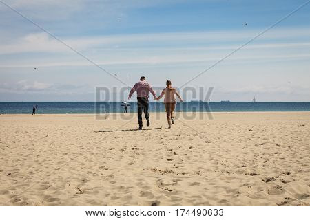 Romance beautiful relantionship concept. Happy couple having date on beach near sea running on sand.