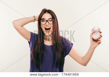 Young Fun Woman In Glasses With Alarmclock. Emotion Smile