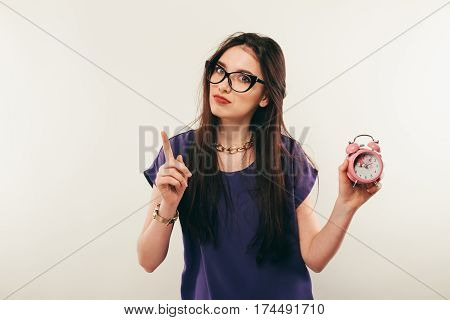 Young Fun Woman In Glasses With Alarmclock. Emotion.