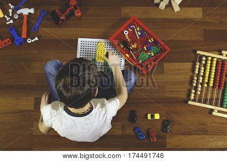 Kid playing with toys tool kit while sitting on the floor in his room. Boy have lots of toys around him. Top view