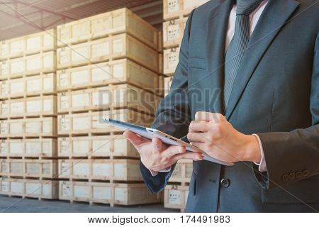 Double exposure of businessman touching tablet analyze and checking stock at transportation port with blurred cargo warehouse background international transportation trading business concept