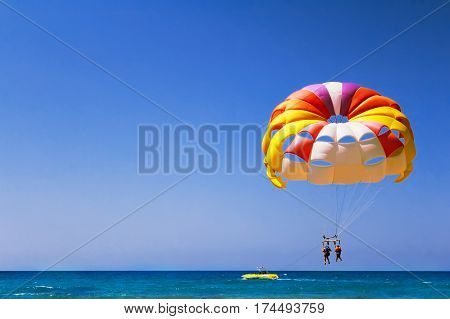 A large parachute with two girls flies in the air over the sea.